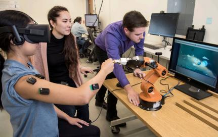 student wearing sensors moves arm while others look at computer screen